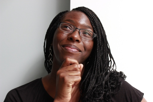 (Image description: a young bespectacled Black woman, her hand under her chin, looks toward the upper left while smiling at the camera; she has braids, a black shirt, and silver swirly earrings. Photo credit: Logan Peters)